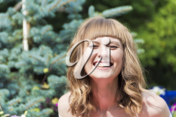 Portrait of laughing young woman with blond hair on summer background