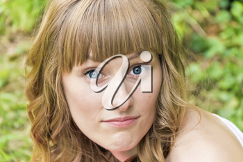Horizontal portrait of young woman with big bulging blue eyes on summer background