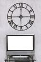 mitnight time on wall clock under blank white screen of TV set