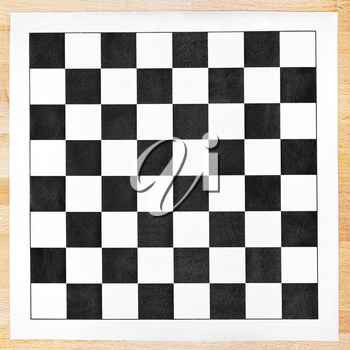 vinyl chessboard with black and white checks on wooden table