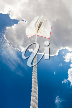 book tied on cord soars into dark blue sky
