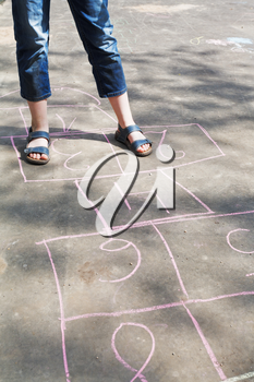 girl playing in hopscotch outdoors in sunny day