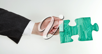 green painted puzzle piece in male hand on grey background