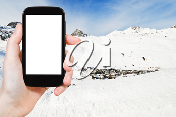 travel concept - tourist photograph view of town Tighnes between snow mountains in Paradiski region, Val d Isere - Tignes, France on tablet pc with cut out screen with blank place for advertising logo