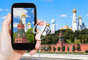 travel concept - tourist photographs picture of Ivan The Great bell tower in Moscow Kremlin on smartphone