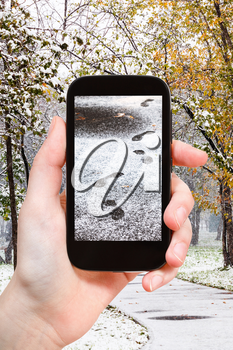 season concept - man taking picture of footprints of steps in first snow in city park on smartphone