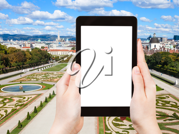 travel concept - tourist photographs lawns of Belvedere Palace in Vienna on tablet pc with cut out screen with blank place for advertising logo