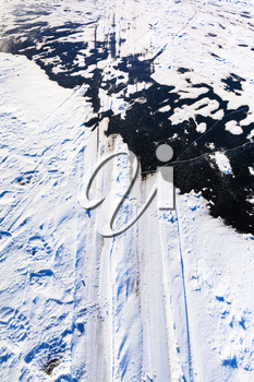 ski tracks on surface of frozen river in cold winter day