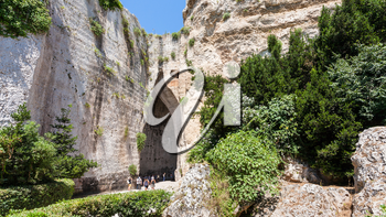travel to Italy - tourists near Orecchio di Dionisio (Ear of Dionysius) cave in Temenites Hill in latomie del paradiso area of Archaeological Park of Syracuse city in Sicily