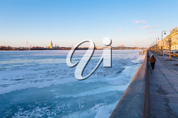 Dvortsovaya Embankment along frozen Neva river and view of Peter and Paul Fortress in Saint Petersburg city in March evening