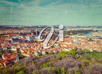 Vintage retro hipster style image of aerial view of Hradchany the Saint Vitus Cathedral and Prague Castle from Petrin Observation Tower with grunge texture overlaid. Prague, Czech Republic