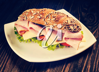 Vintage retro effect filtered hipster style image of ham sandwich with lettuce, cheese, tomato on plate on wooden table