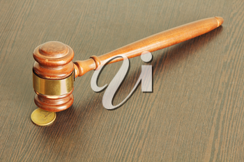 Auction hammer or judge gavel and one dollar coin on wooden table taken closeup.