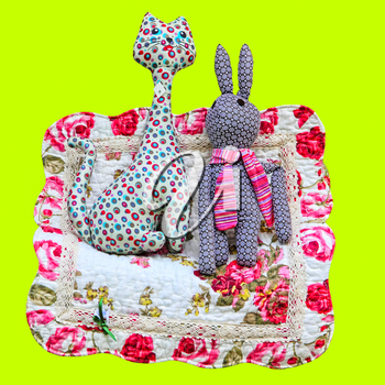 Handmade cat and rabbit toys on yellow background.