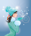 Beautiful brunette girl with warm blue winter hat is blowing snow from her hands (snowflakes in heart shape)