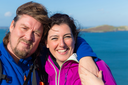 Young trendy smiling and hugging couple in Ireland wearing outdoor gear with the Irish sea in the background