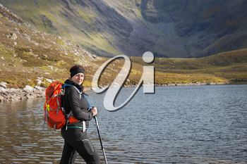 Female trekker with trekking poles and backpack posing lake side with the Macgillycuddy's Reeks  mountain range in the background