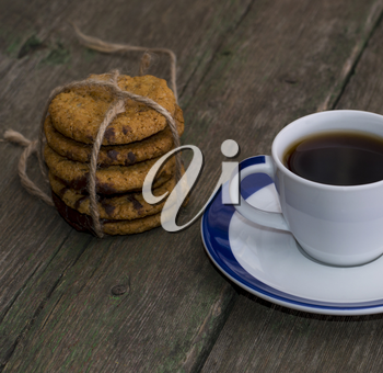 cup of black coffee and linking of cookies on the old desktop