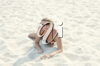 the beautiful woman lies on a beach in sand