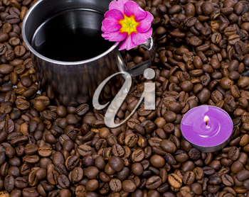 lilac candle and steel cup of coffee in coffee grains, a subject drinks