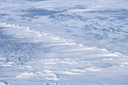 Snow hummocks on the surface of frozen reservoir