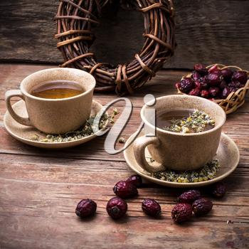 Two ceramic cups brewed tea with rosehip and chamomile amid bundles of licorice root