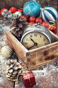 Retro alarm clock in  wooden box in the composition with Christmas decorations.