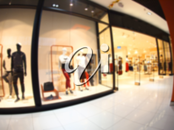 Defocused and blur image of a large shopping mall hall with glass display cases and mannequins with wide angle fisheye lens and distortion view. The image was blurry for use as background