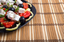 Side view of the Greek vegetarian salad of tomatoes, cucumbers, onions, olives, peppers and feta cheese in a black plate on a bamboo mat closeup