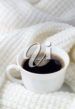 White cup with hot coffee wrapped in a white woolen scarf with shallow depth of focus.