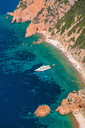 Luxury white pleasure yacht anchored near rocky beach of Corsica island, vertical photo, birds eye view