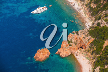 Luxury white pleasure yacht anchored near rocky beach of Corsica island, birds eye view
