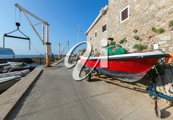 Red fishing boat stands on the coast in port of Petrovac, Montenegro