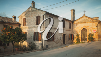 Street view of Fermo town with old living houses at evening, Italy. Vintage toned photo