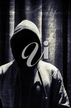 Portrait of incognito man under hood with grunge curtain background