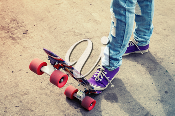 Teenager feet in blue jeans and gumshoes on a skateboard, photo with warm retro tonal correction, old style