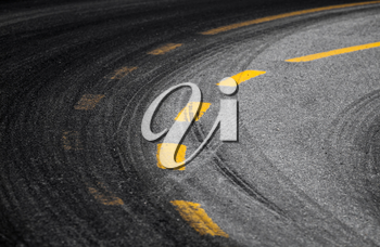 Abstract turning road background with tires track and yellow striped road marking on dark asphalt