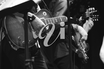 Rock and roll music background, guitar players on a stage, selective focus