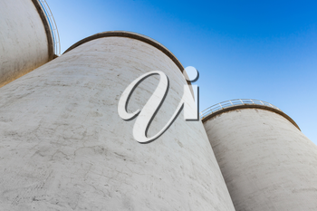 Abstract industrial architecture fragment, large tanks made of concrete for storage of bulk materials under blue sky