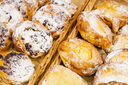 Sweet buns with berries and sugar powder lay on shelves of bakery shop