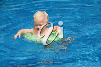 Baby swimming in the blue pool water