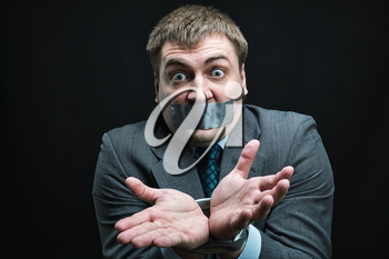 Businessman with mouth and hands  covered by masking tape preventing speech, studio shoot