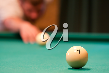 Billiard player concentrating and aiming to ball