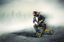 Odd businessman riding a small bicycle against dark city