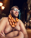 Cool man in glasses with sausages on his neck sits in the evening city