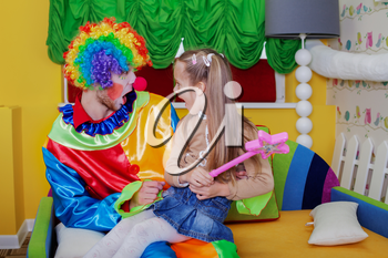 Little girl sitting on the lap of a cheerful clown with funny makeup. Children's friendship forever.