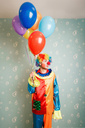 Dull clown with a bunch of colourful air balloons standing in the room.