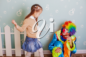 During the game a little girl hits upset clown. Decoration room on the background.