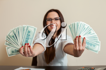 Business woman with money fans in hands. Happy female accountant holding dollars in her hand.