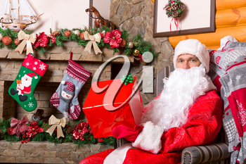 Bearded Father Christmas in red costume with gift box sitting in a chair, fireplace and holiday decoration on background
